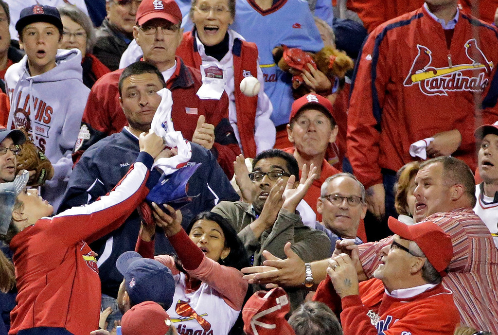 . Fans go after a foul ball hit by Boston Red Sox\'s Stephen Drew during the seventh inning of Game 5 of baseball\'s World Series against the St. Louis Cardinals Monday, Oct. 28, 2013, in St. Louis. (AP Photo/David J. Phillip)