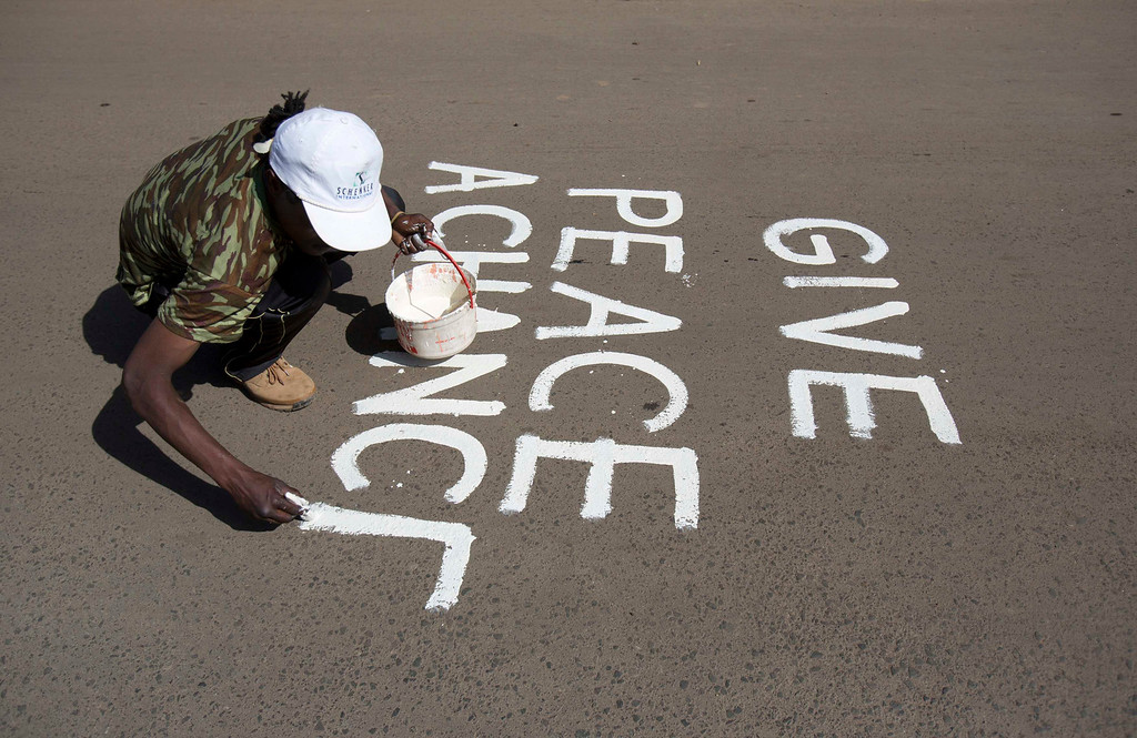 . An artist known as solo7 paints a peace message on the tarmac in the Kibera slum in the Kenyan capital of Nairobi March 9, 2013.    REUTERS/Karel Prinsloo