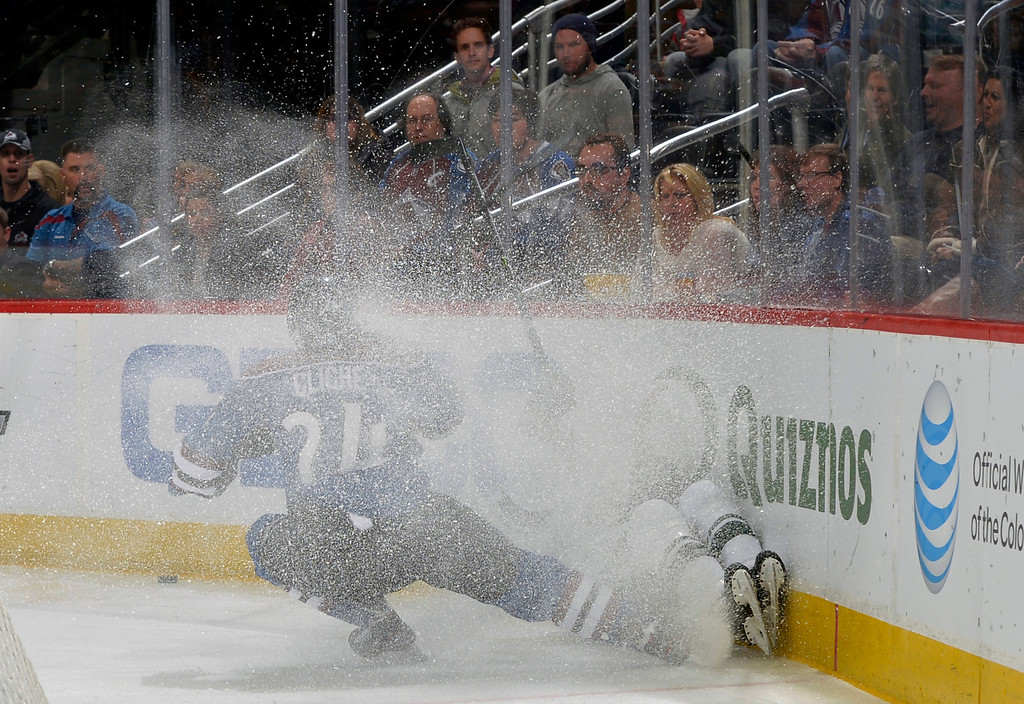 . Colorado Avalanche right wing Marc-Andre Cliche (24) drives a Minnesota Wild player into the boards in a spray of ice during the first period of an NHL hockey game on Saturday, Nov. 30, 2013, in Denver. (AP Photo/Jack Dempsey)