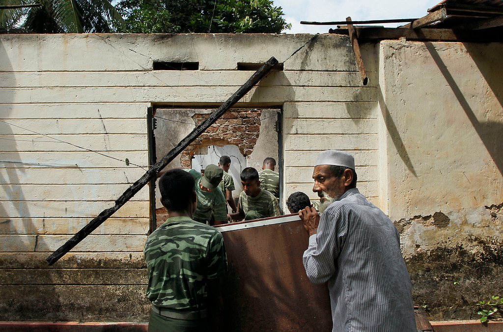 . In this Friday, June 27, 2014 photo, a Sri Lankan Muslim man helps army soldiers salvage damaged household items from the debris of a burnt house in Darga Town in Aluthgama about 50 kilometers (31 miles) south of Colombo, Sri Lanka. The onslaught by the Bodu Bala Sena (BBS), a hardline Buddhist group, killed two Muslims in the worst religious violence Sri Lanka has seen in decades. (AP Photo/Eranga Jayawardena)