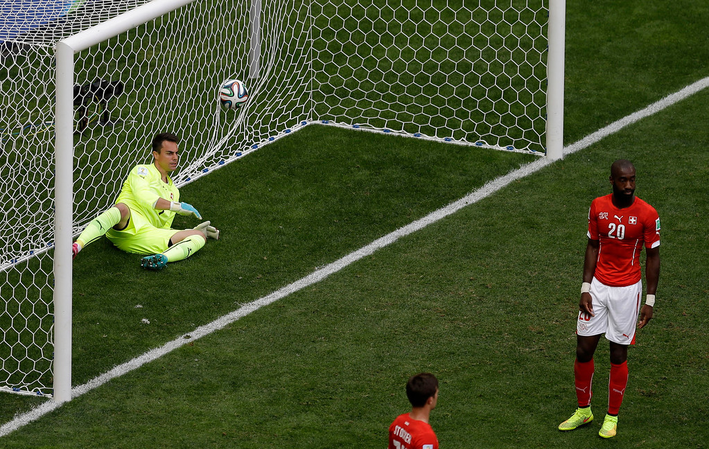 . Switzerland\'s goalkeeper Diego Benaglio, left, sits in the goal after Ecuador scored their first goal during the group E World Cup soccer match between Switzerland and Ecuador at the Estadio Nacional in Brasilia, Brazil, Sunday, June 15, 2014. (AP Photo/Themba Hadebe)