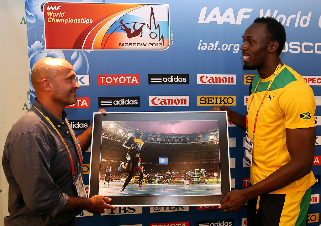 . AFP photographer Oliver Morin (L) gives Jamaica\'s Usain Bolt a print of a picture he took of him during the 100m final prior to a press conference at the Luzhniki stadium in Moscow during the World Athletics Championships on August 17, 2013.  FRANCK FIFE/AFP/Getty Images