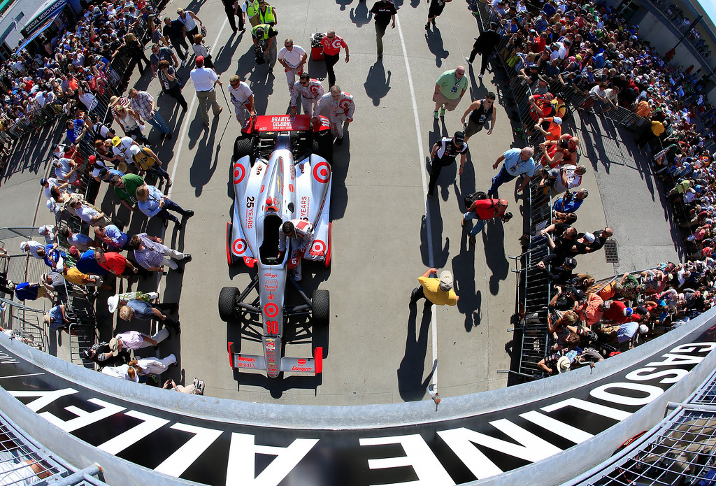 . Crew members push the car of Tony Kanaan, driver of the #10 Target Chip Ganassi Racing Honda, through gasoline alley toward the grid prior to the 98th running of the Indianapolis 500 Mile Race at Indianapolis Motorspeedway on May 25, 2014 in Indianapolis, Indiana.  (Photo by Jamie Squire/Getty Images)