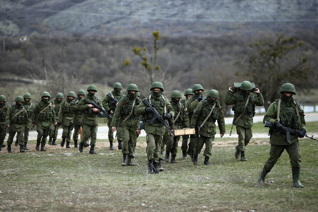 . Russian military personnel move towards a Ukrainian military base on March 19, 2014 in Perevalnoe, Ukraine. Russia\'s Constitutional Court ruled unanimously on March 19 that Russia\'s President Vladimir Putin acted legally by signing a treaty to make Crimea part of Russia.  (Photo by Dan Kitwood/Getty Images)
