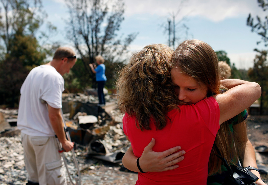 . Krista Albers, 19, facing camera, hugs family friend Joie Edwards after seeing the remnants of her family\'s home in the Mountain Shadows subdivision on Sunday, July 1, 2012. Stephen Mitchell, The Denver Post