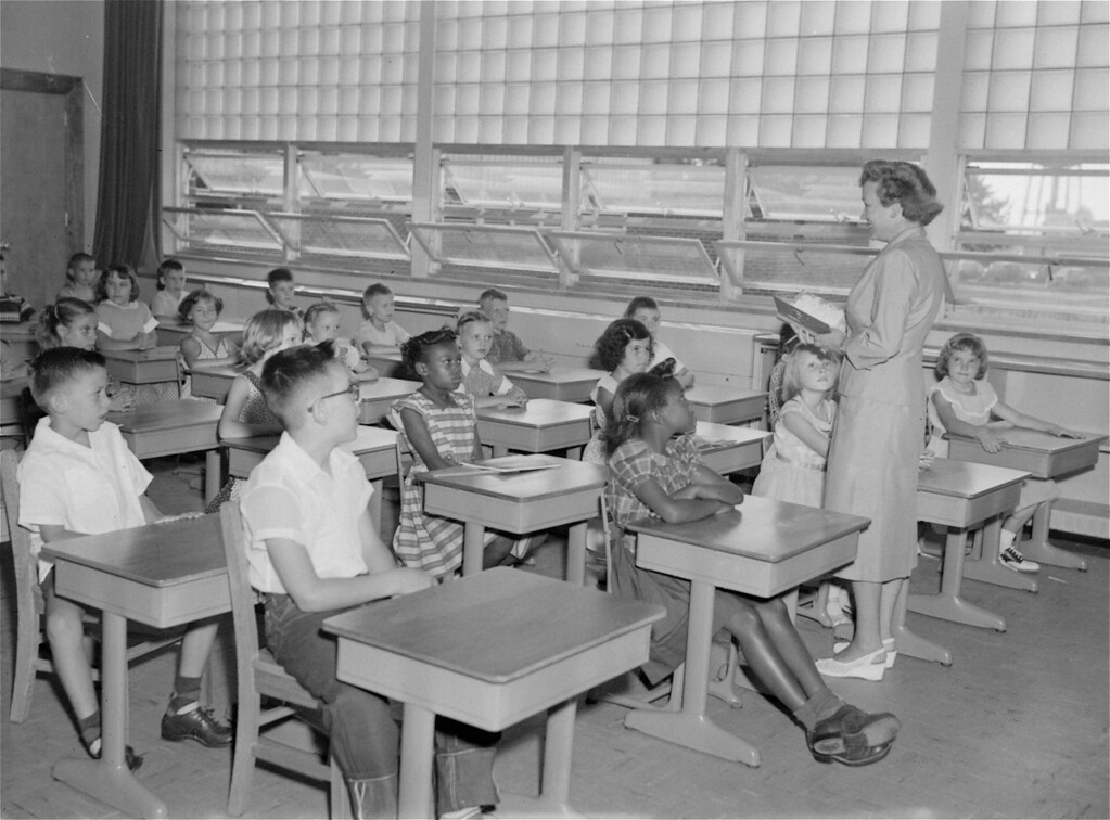 . Two of six black children who joined classes in the formerly all white Ft. Myer, VA elementary school listen to opening announcements by Mrs. Louise M. Snee, third grade teacher, at the school opening September 7, 1954.  The children are Breda Hines, 8, front row, and Lillie Mae Gilliard, second row.  There are 380 pupils in the federally operated school on the military post, and six are black.  (AP Photo)