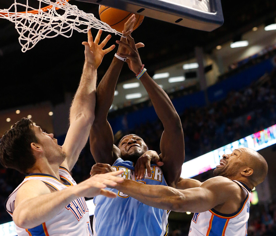 . Denver Nuggets forward Kenneth Faried, center, loses the ball while defended by Oklahoma City Thunder forward Nick Collison (4) and guard Derek Fisher  in the first quarter of an NBA basketball game in Oklahoma City, Monday, March 24, 2014. (AP Photo/Sue Ogrocki)