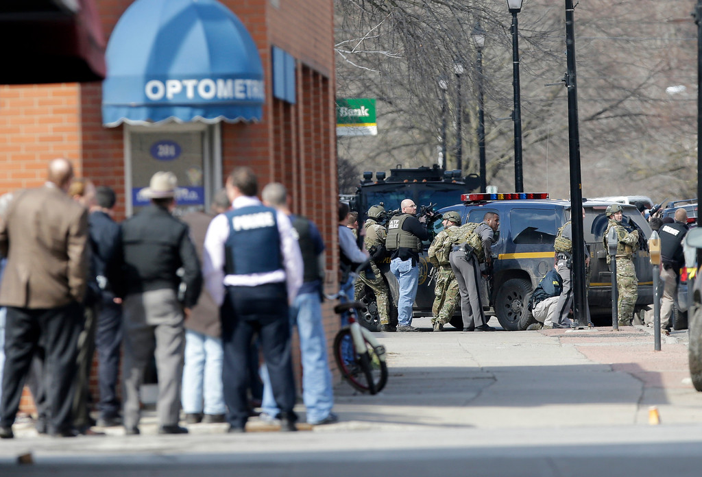 . Law enforcement officers take cover along Main Street when shots were fired while searching for a suspect in two shootings that killed four and injured at least two on Wednesday, March 13, 2013, in Herkimer, N.Y. (AP Photo/Mike Groll)