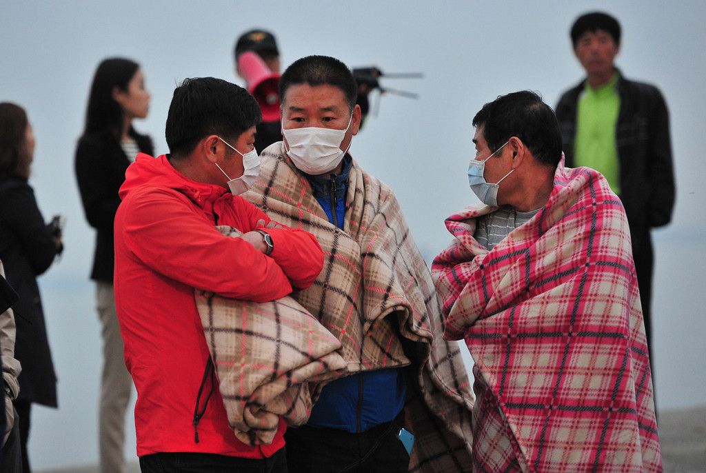 . South Korean relatives wait for missing people at a harbor in Jindo on April 16, 2014 as South Korean rescue teams, including elite navy SEAL divers, raced to find up to 293 people missing from a capsized ferry carrying 459 passengers and crew -- mostly high school students bound for a holiday island.  Two people -- a male student and a female crew member -- were confirmed dead as the vessel sank 20 kilometres (13 miles) off the southern island of Byungpoong.  AFP PHOTO / JUNG YEON-JE/AFP/Getty Images