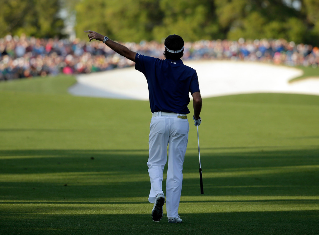 . Bubba Watson points as his ball goes into the gallery on the 18th hole during the third round of the Masters golf tournament Saturday, April 12, 2014, in Augusta, Ga. (AP Photo/Chris Carlson)