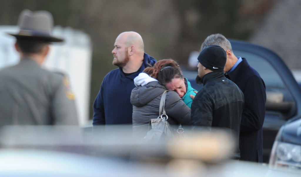 . Police stand before grieving residents following a shooting December 14, 2012 at Sandy Hook Elementary School on December 14, 2012 in Newtown, Connecticut. At least 26 people, including 20 young children, were killed when a gunman assaulted the school and another body was found dead at a second linked crime scene, police said.  Police spokesman Lieutenant Paul Vance told reporters that the attacker killed 20 children and six adults, including someone that he lived with, at the Sandy Hook Elementary School in Newtown, Connecticut.  The gunman also died at the scene, and a 28th body was found elsewhere.    AFP PHOTO / Don EMMERTDON EMMERT/AFP/Getty Images