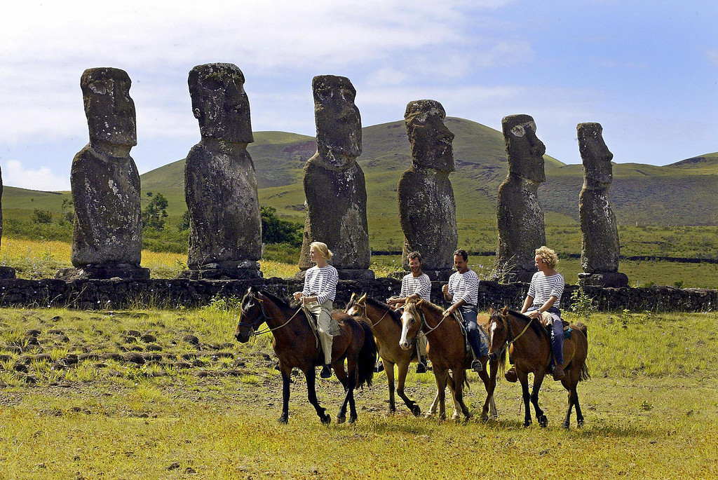 . (L to R) The crew of French research and exploration ship La Boudeuse Julia Dudrait, Bruno Tomasi, Captain Patrice Franceschi (2nd R)and Pierre Marcel ride horses in front of the Moais monoliths, in the Ahu Akivi area of the Eastern Island, Chile, 04 February 2005. MARTIN BERNETTI/AFP/Getty Images