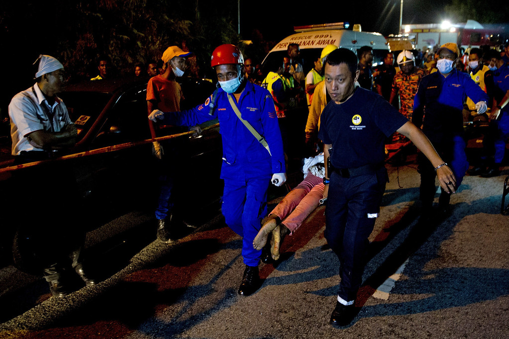 . Malaysian emergency services personnel carry a dead passenger after a bus carrying tourists and local residents fell into a ravine near the Genting Highlands, about an hour\'s drive from Kuala Lumpur on August 21, 2013.    AFP PHOTO / MOHD RASFAN/AFP/Getty Images
