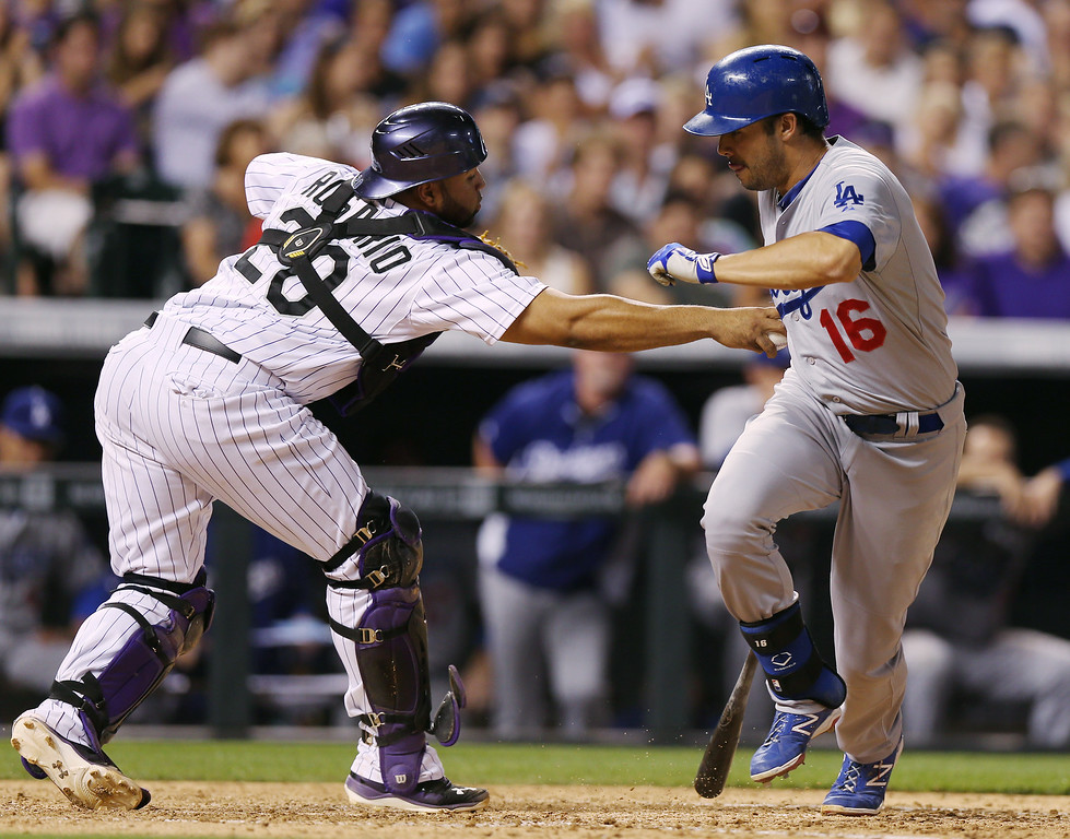 . Colorado Rockies catcher Wilin Rosario, left, tags out Los Angeles Dodgers pinch hitter Andre Ethier after Ethier struck out but Rosario dropped the pitch to end the top of the ninth inning of the Dodgers\' 3-2 victory in a baseball game in Denver, Thursday, July 3, 2014. (AP Photo/David Zalubowski)