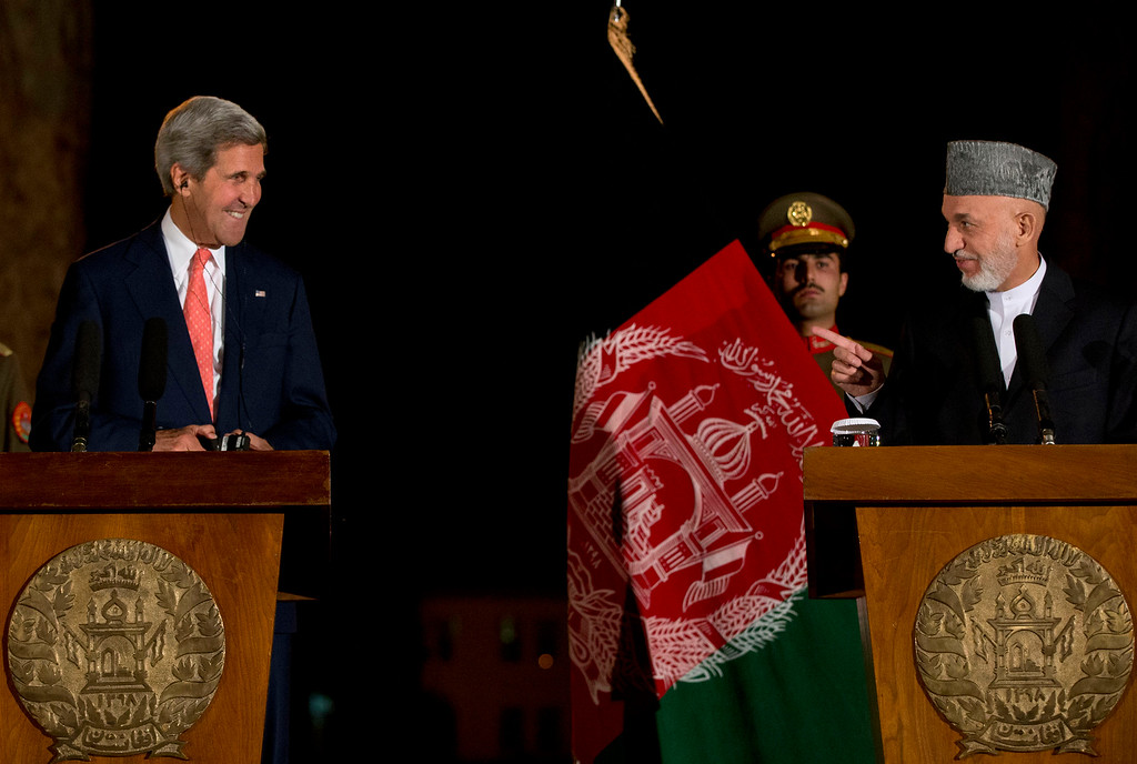 . Afghan President Hamid Karzai, right, points toward U.S. Secretary of State John Kerry as he jokes with him at the start of a news conference at the Presidential Palace during Kerry\'s unannounced stop in Kabul, Afghanistan, on Saturday, Oct. 12, 2013, as a deadline approaches for a security deal about the future of U.S. troops in the country. (AP Photo/Jacquelyn Martin, Pool)