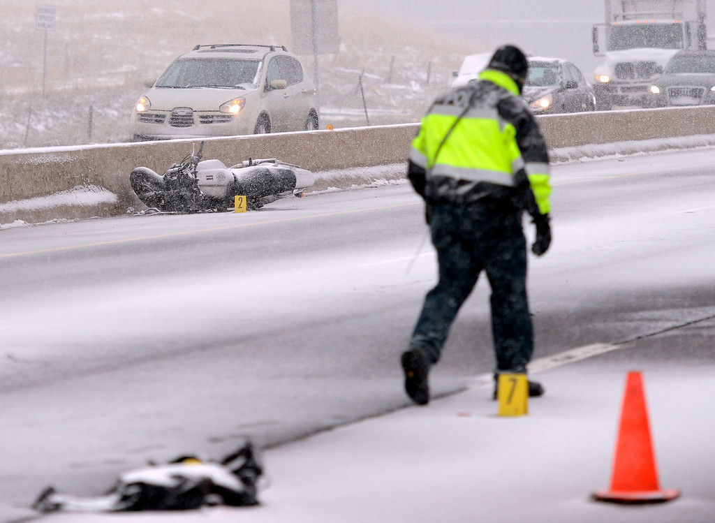 . Police investigate a fatal motorcycle accident that shuts down westbound lanes of U.S. 36, April 15, 2013. Snow continues to fall in the area. (Photo By RJ Sangosti/The Denver Post)