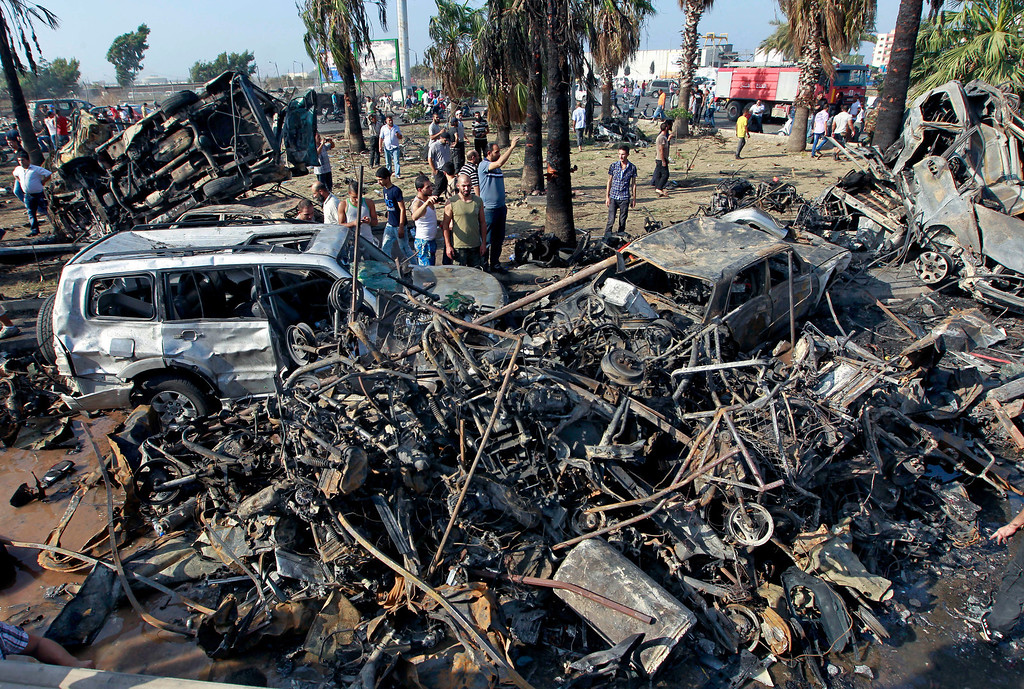 . People gather outside the Al-Taqwa Mosque the amid charred cars and wide damage, in the northern city of Tripoli, Lebanon, Friday, Aug. 23, 2013. (AP Photo/Bilal Hussein)