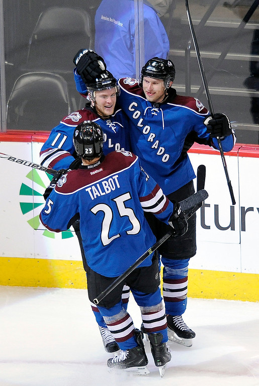 . Colorado Avalanche left wing Jamie McGinn, left, center Maxime Talbot, bottom left, and defenseman Erik Johnson, right, celebrate a goal by Johnson in the third period of an NHL hockey game against the Tampa Bay Lightning on Sunday, March 2, 2014 in Denver. The Avalanche won 6-3. (AP Photo/Chris Schneider)