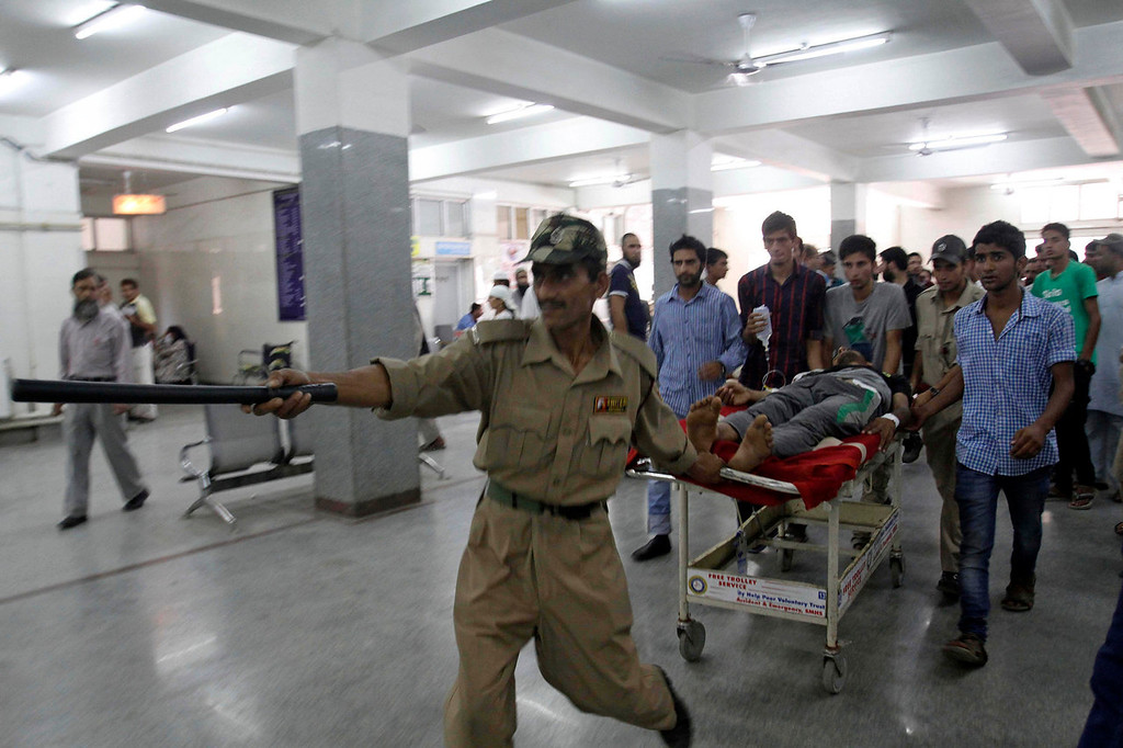 . A policeman clears the way for a stretcher carrying Adil Ahmed, injured in a shootout at Shopian, at a hospital in Srinagar, India, Saturday, Sept. 7, 2013. Hundreds of people protested Saturday after Indian police killed at least two men they described as militants in the disputed Himalayan territory of Kashmir. Ahmed, a 26-year-old student shot twice in the stomach, said at a hospital that the two men killed were not militants but students riding a motorcycle to an exam center to take tests. (AP Photo/Mukhtar Khan)