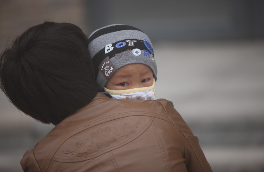 . A woman and her son wearing masks walk along a road as heavy smog engulfs the city on October 21, 2013 in Changchun, China.  (Photo by ChinaFotoPress/Getty Images)