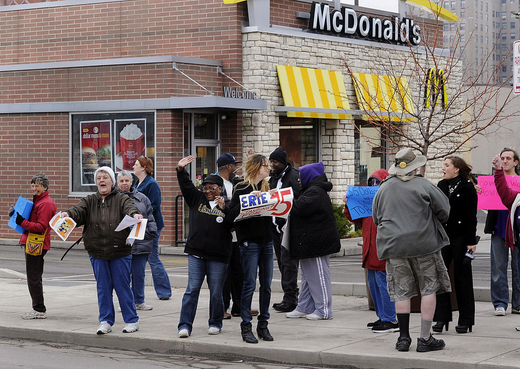 . Protesters, for higher minimum wages, wave to passing motorists while picketing in front of a McDonald\'s restaurant in Erie, Pa., on Thursday, Dec. 5, 2013. The protest was part of a national campaign to increase the minimum wage.  (AP Photo/Erie Times-News, Christopher Millette)