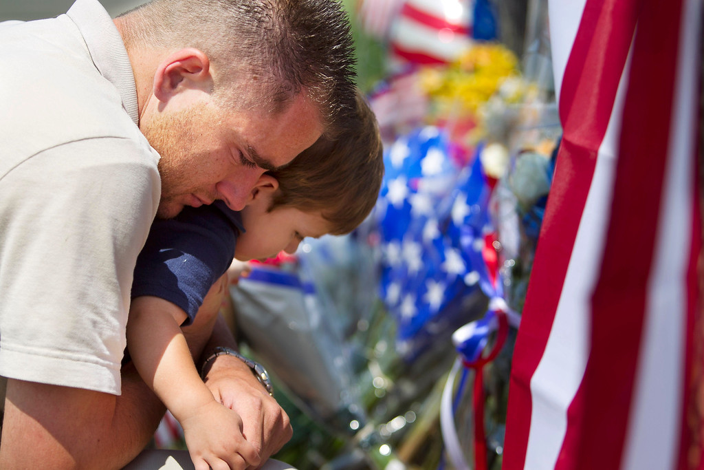 . Duane Oliver of Prescott Valley hugs his son, Conner Oliver, 2, by a memorial for the fallen firefighters in front of Prescott Fire Station #7 on Monday, July 1, 2013. Nineteen firefighters have died in the Yarnell Hill Fire that has ripped through half of the town and sent residents to Prescott for safety. (AP Photo/The Arizona Republic, David Wallace)
