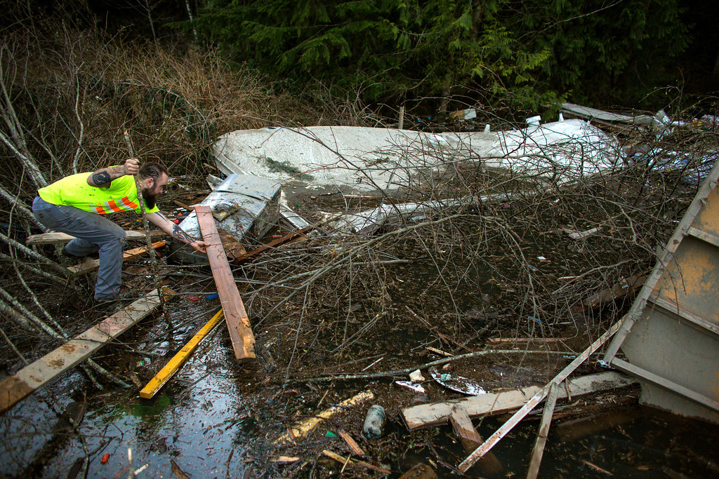 . Iraq War veteran and local Little League coach Matt Pater, 32, creates a bridge to check a floating section of a home in a field of debris following Saturday\'s destructive mudslide, near Oso Wash, Monday, March 24, 2014. (AP Photo/seattlepi.com, Joshua Trujillo)