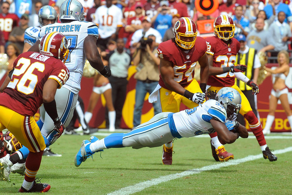 . Detroit Lions running back Joique Bell dives into the end zone past Washington Redskins linebacker Darryl Tapp (54) and cornerback David Anderson (39) during the first half of a NFL football game in Landover, Md., Sunday Sept. 22, 2013. (AP Photo/Richard Lipski)