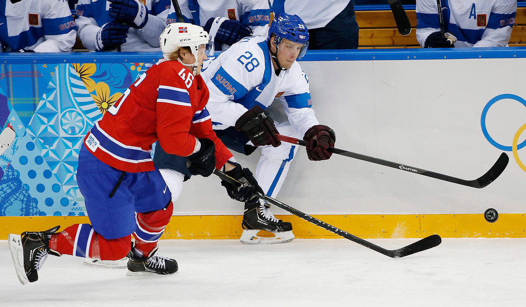 . Norway forward Mathis Olimb and Finland forward Lauri Korpikoski chase a loose puck during the 2014 Winter Olympics men\'s ice hockey game at Shayba Arena, Friday, Feb. 14, 2014, in Sochi, Russia. (AP Photo/Petr David Josek)