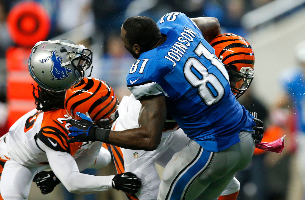 . Detroit Lions wide receiver Calvin Johnson (81) loses his helmet trying to catch a pass while being hit by Cincinnati Bengals strong safety George Iloka (43)  as safety Reggie Nelson (20) moves in to help in the second quarter of an NFL football game against Sunday, Oct. 20, 2013, in Detroit. (AP Photo/Rick Osentoski)