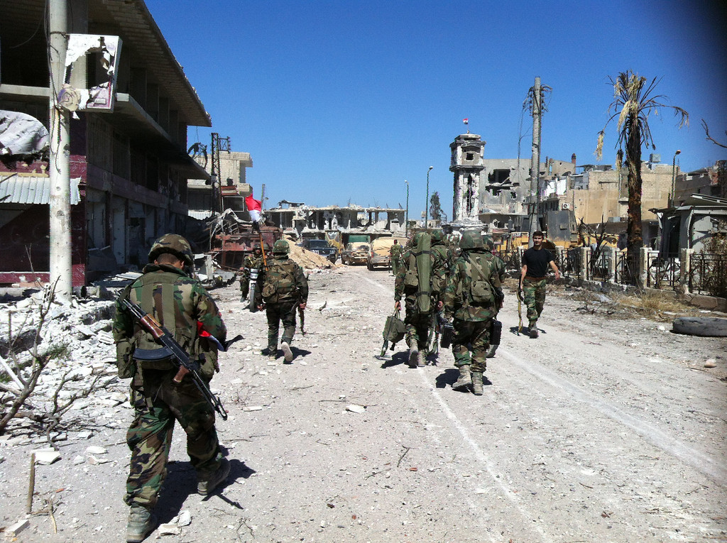 . Syrian army\'s soldiers walk in a street left in ruins on June 5, 2013 in the city of Qusayr in Syria\'s central Homs province, after the Syrian government forces seized total control of the city and the surrounding region. The Syrian army ousted rebels from the strategic town of Qusayr after a blistering 17-day assault led by Hezbollah fighters, scoring a major battlefield success in a war that has killed at least 94,000 people.   AFP PHOTO / STR-/AFP/Getty Images
