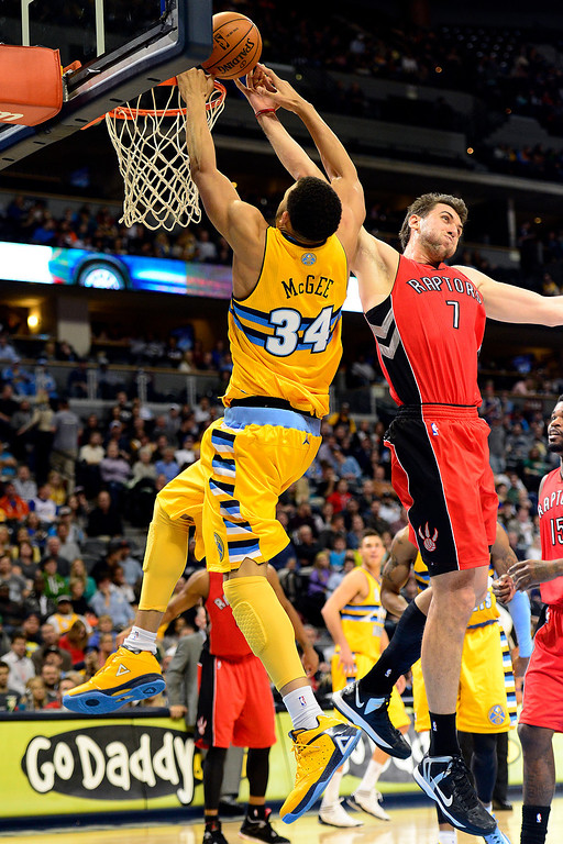. Denver Nuggets center JaVale McGee (34) is fouled by Toronto Raptors center Andrea Bargnani (7) during the first half at the Pepsi Center on Monday, December 3, 2012. AAron Ontiveroz, The Denver Post