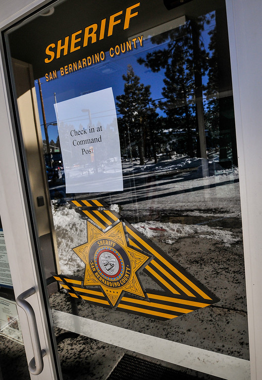 . A sign placed on front door at the Big Bear Sheriff\'s Station directs authorities to check in at the command post near Bear Mountain Resort as day four of the search for fugitive ex-cop Christopher Dorner continues in Big Bear on Sunday, Feb. 10, 2013. (Rachel Luna / Staff Photographer)