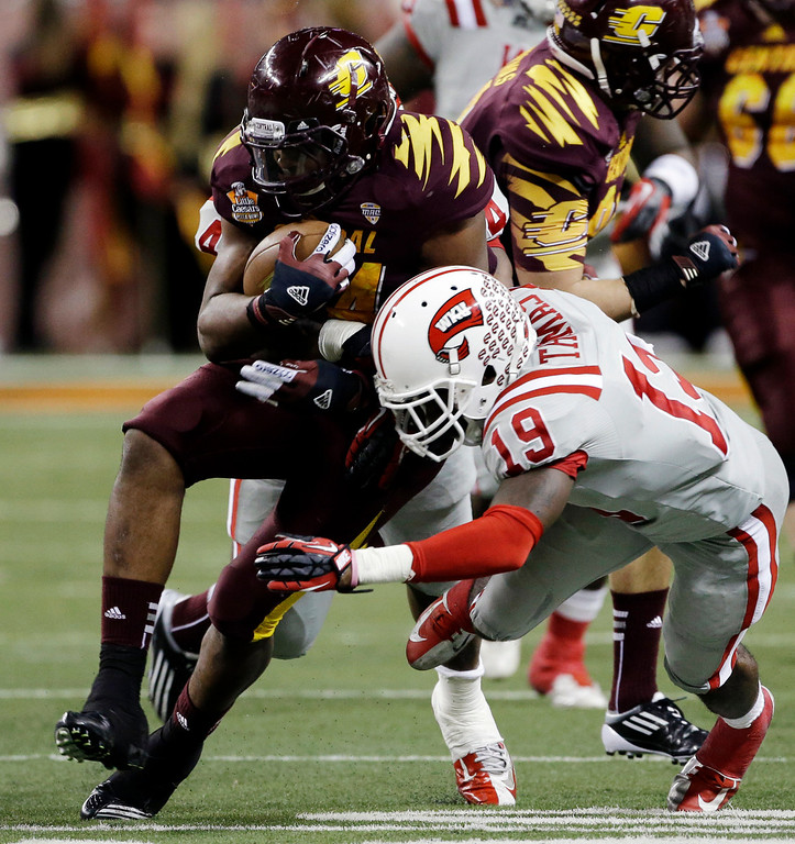 . Central Michigan running back Zurlon Tipton (34) is stopped by Western Kentucky defensive back Cam Thomas (19) during the second quarter of the Little Caesars Pizza Bowl NCAA college football game at Ford Field in Detroit, Wednesday, Dec. 26, 2012. (AP Photo/Carlos Osorio)