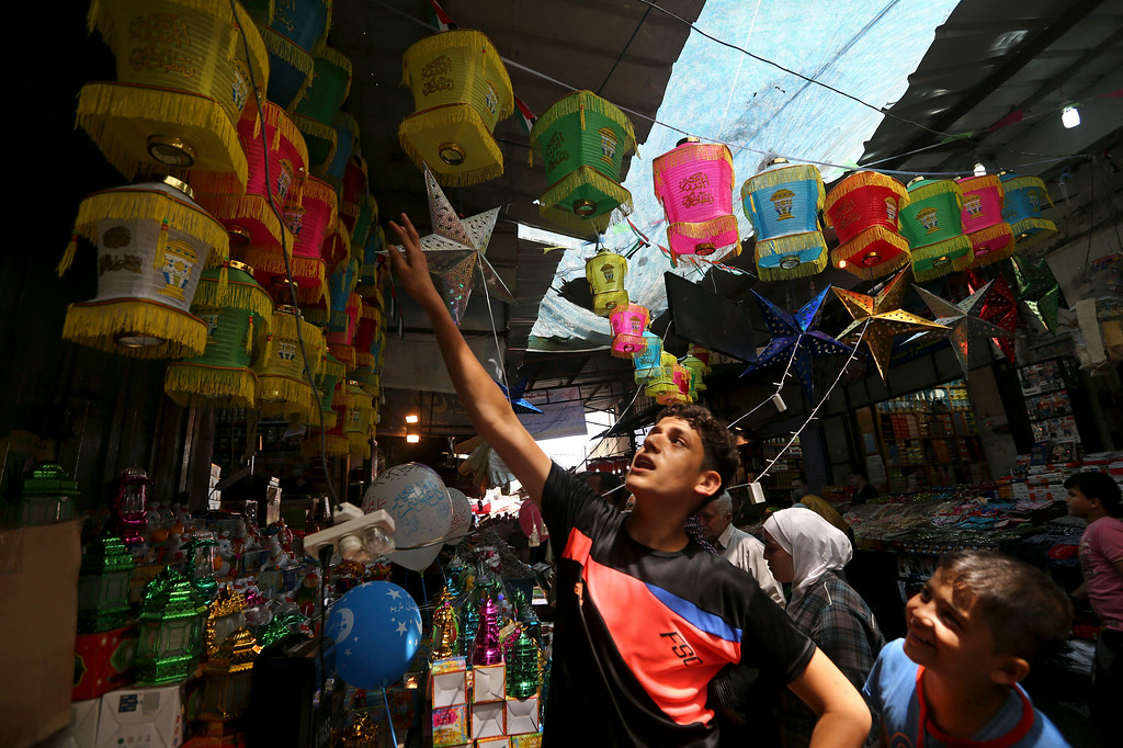 . Palestinian shop for imported traditional Ramadan lanterns at a market in Gaza City on Saturday, June 28, 2014. Starting on Sunday, Muslims around the world will mark the beginning of the holy fasting month of Ramadan where the devout fast from dawn until dusk. (AP Photo/Hatem Moussa)