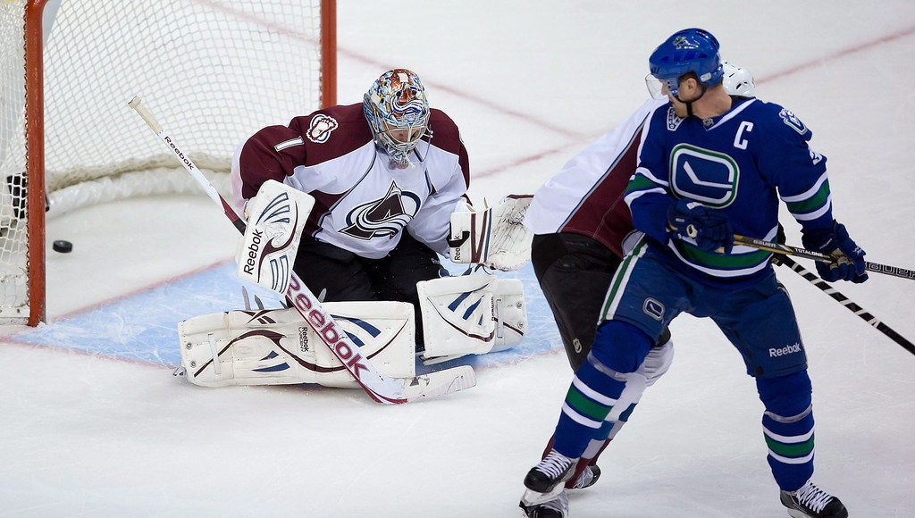 . Colorado Avalanche goalie Semyon Varlamov, left, of Russia, allows a goal to Vancouver Canucks\' Daniel Sedin, of Sweden, unseen, as his Henrik Sedin, of Sweden, watches during the third period of an NHL hockey game in Vancouver, British Columbia, on Thursday, March 28, 2013. (AP Photo/The Canadian Press, Darryl Dyck)