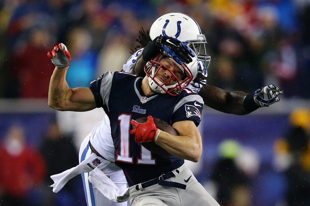 . FOXBORO, MA - JANUARY 11:  Julian Edelman #11 of the New England Patriots runs the ball against Erik Walden #93 of the Indianapolis Colts in the first quarter during the AFC Divisional Playoff game at Gillette Stadium on January 11, 2014 in Foxboro, Massachusetts.  (Photo by Al Bello/Getty Images)