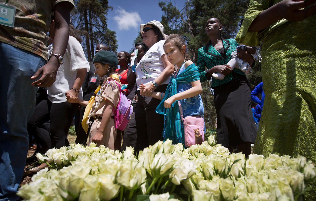 . Relatives and friends of those who died walk past white roses, which they later laid at a stone memorial, during a memorial service marking the one-month anniversary of the the Sept. 21 Westgate Mall terrorist attack, in Karura Forest in Nairobi, Kenya Monday, Oct. 21, 2013. (AP Photo/Ben Curtis)