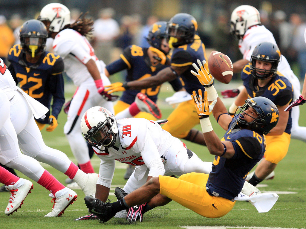 . West Virginia\'s Terrell Chestnut (16) forces a fumble on a kickoff return from Texas Tech\'s Austin Stewart (30) during the second quarter of their NCAA college football game in Morgantown, W.Va., on Saturday, Oct. 19, 2013. (AP Photo/Christopher Jackson)