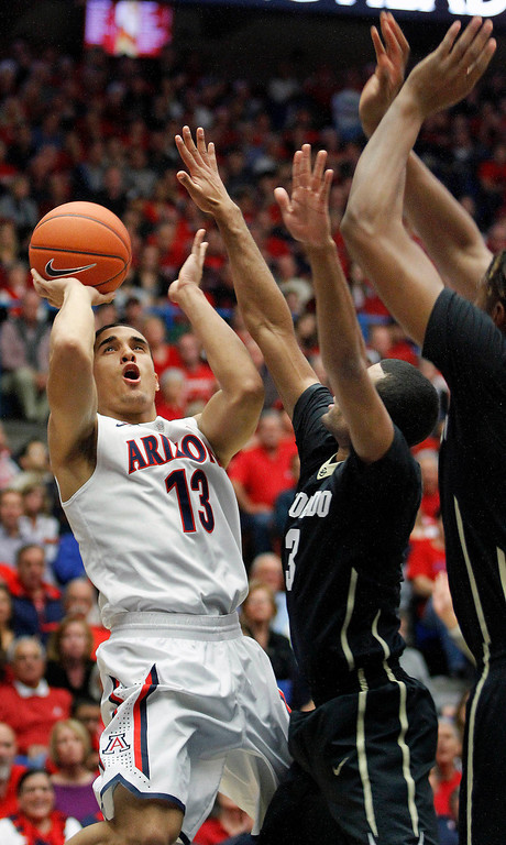 . Arizona\'s Nick Johnson (13) shoots for two against the defense of Colorado\'s Xavier Talton (3) and Xavier Johnson, far right, in the first half of an NCAA college basketball game, Thursday, Jan. 23, 2014 in Tucson, Ariz. (AP Photo/John Miller)