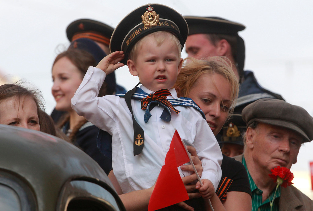 . A child wearing Soviet Navy style uniform salutes during celebration of the Victory Day in St.Petersburg, Russia, Thursday, May 9, 2013. Russia is celebrating the anniversary of victory over Germany in WWII.  (AP Photo/Dmitry Lovetsky)
