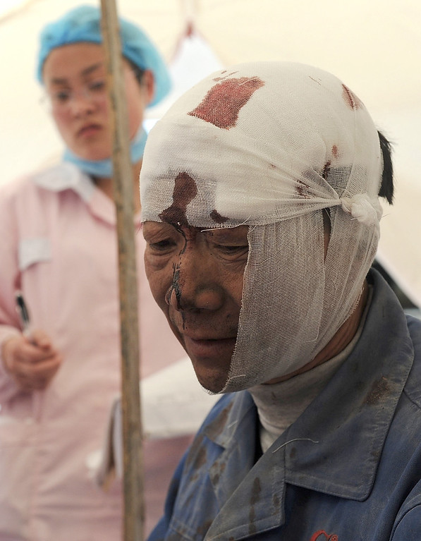 . An injured man rests at a temporary treatment station following an earthquake in Lushan county in Ya\'an in southwest China\'s Sichuan province Saturday, April 20, 2013. The powerful earthquake shook Chinaís Sichuan province Saturday morning, nearly five years after a devastating quake jolted the province. (AP Photo)