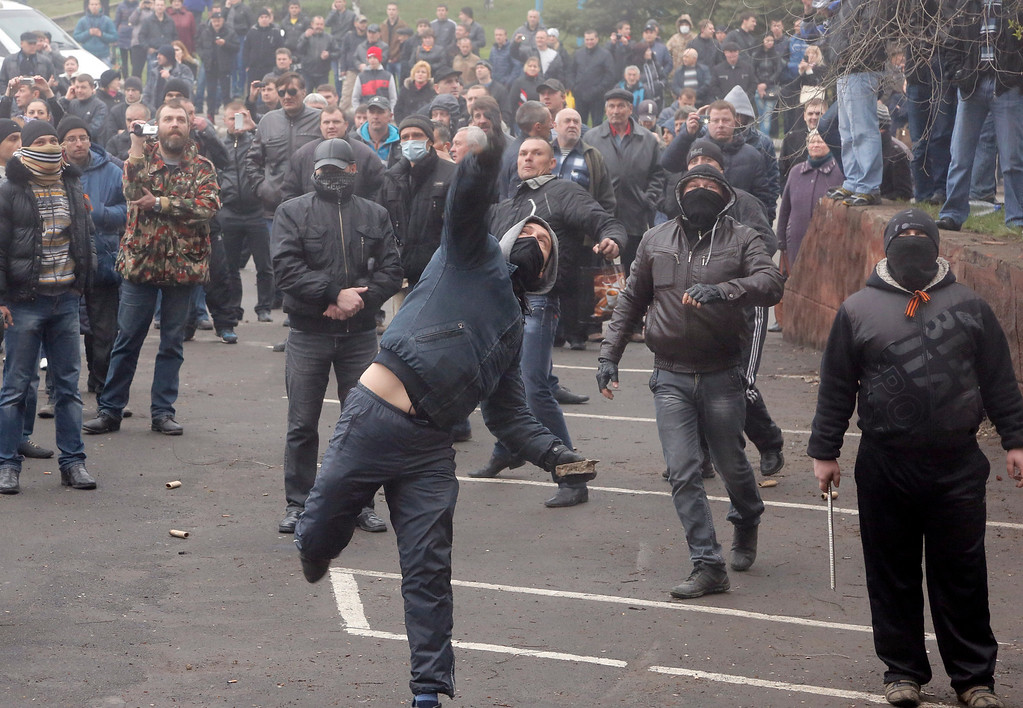 . Pro-Russian men throw  stones during the mass storming of a police station in the eastern Ukrainian town of Horlivka Monday, April 14, 2014.    (AP Photo/Efrem Lukatsky)