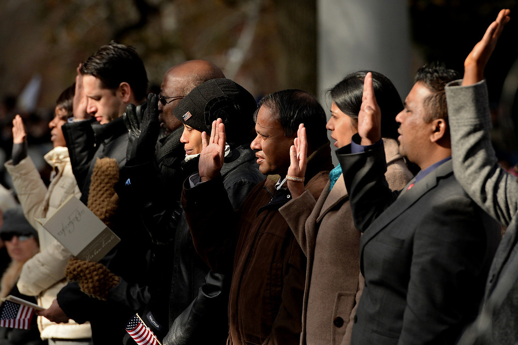 . People take oath in a U.S. naturalization ceremony during a commemoration of the 150th Anniversary of the Gettysburg Address at the Soldiers\' National Cemetery at Gettysburg National Military Park on November 19, 2013 in Gettysburg, Pennsylvania. (Photo by Patrick Smith/Getty Images)