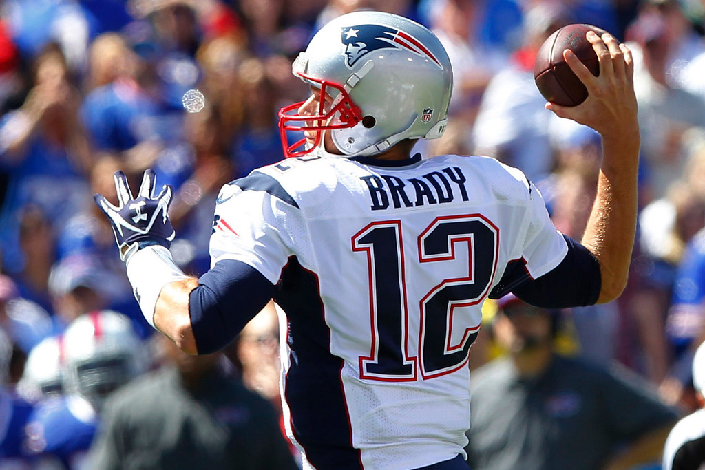 . New England Patriots quarterback Tom Brady (12) throws a touchdown pass to Julian Edelman during the first half of an NFL football game against the Buffalo Bills, Sunday, Sept. 8, 2013, in Orchard Park. (AP Photo/Bill Wippert)
