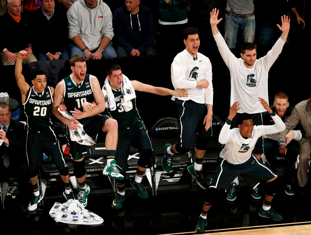 . Michigan State players react during second half in a regional semifinal against Virginia at the NCAA men\'s college basketball tournament, early Saturday, March 29, 2014, in New York. (AP Photo/Julio Cortez)