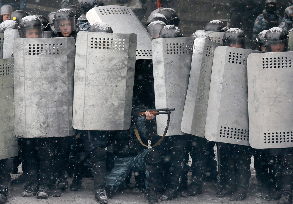 . A police officer aims his shotgun during clashes with protesters in central Kiev, Ukraine, Wednesday, Jan. 22, 2014.  (AP Photo/Efrem Lukatsky)