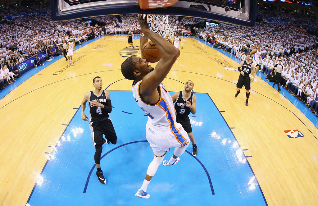 . OKLAHOMA CITY, OK - MAY 31:  Kevin Durant #35 of the Oklahoma City Thunder dunks the ball as Danny Green #4 and Tony Parker #9 of the San Antonio Spurs look on in the first half during Game Six of the Western Conference Finals of the 2014 NBA Playoffs at Chesapeake Energy Arena on May 31, 2014 in Oklahoma City, Oklahoma. (Photo by Ronald Martinez/Getty Images)
