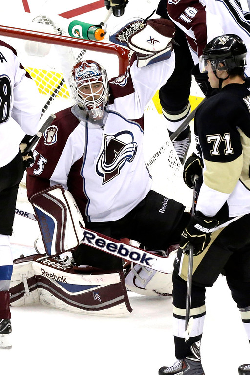 . Colorado Avalanche goalie Jean-Sebastien Giguere (35) celebrates a 1-0 shutout win over the Pittsburgh Penguins as time runs out in the third period of an NHL hockey game in Pittsburgh Monday, Oct. 21, 2013.  At right is Penguins\' Evgeni Malkin (71). (AP Photo/Gene J. Puskar)