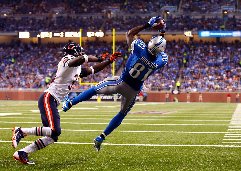 . Detroit Lions wide receiver Calvin Johnson (81), defended by Chicago Bears cornerback Charles Tillman (33),  catches a two-yard touchdown from quarterback Matthew Stafford during the second quarter of an NFL football game at Ford Field in Detroit, Sunday, Sept. 29, 2013. (AP Photo/Jose Juarez)